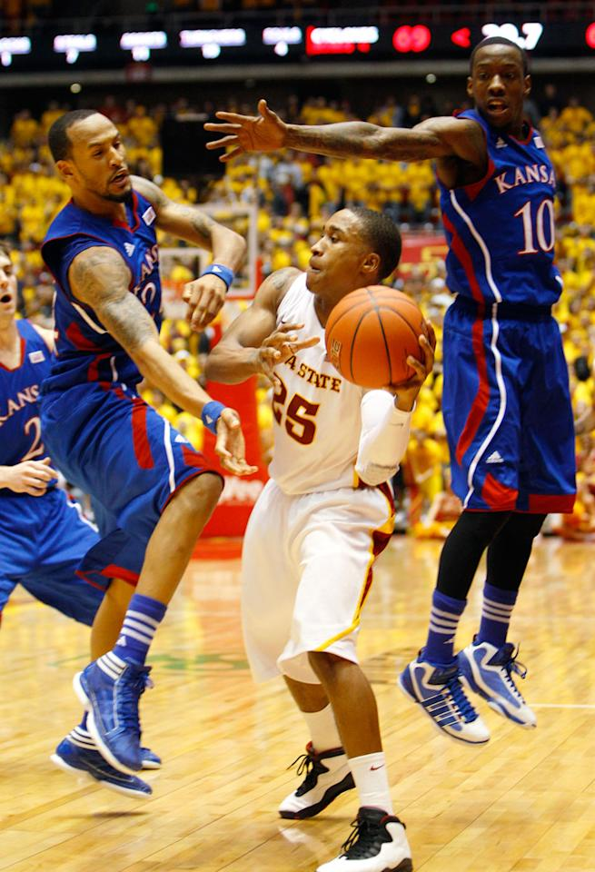 Iowa State guard Tyrus McGee (25) passes the ball between Kansas defenders Travis Releford, left, and Tyshawn Taylor, right, during second half of an NCAA college basketball game, Saturday, Jan. 28, 2012, in Ames, Iowa. Iowa State won 72-64.