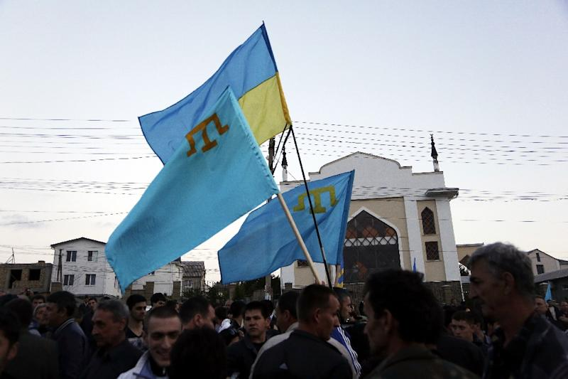 Crimean Tatars hold Ukrainian and Tatar flags as they attend a memorial ceremony marking the 70th anniversary of the deportation of Tatars from Crimea, in Simferopol on May 17, 2014 (AFP Photo/Max Vetrov)