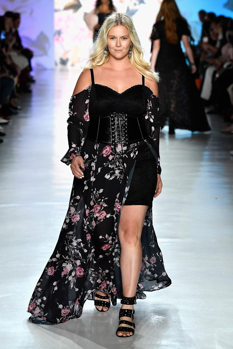 Model wears a corset around a black floral-print maxidress at the Torrid NYFW show.