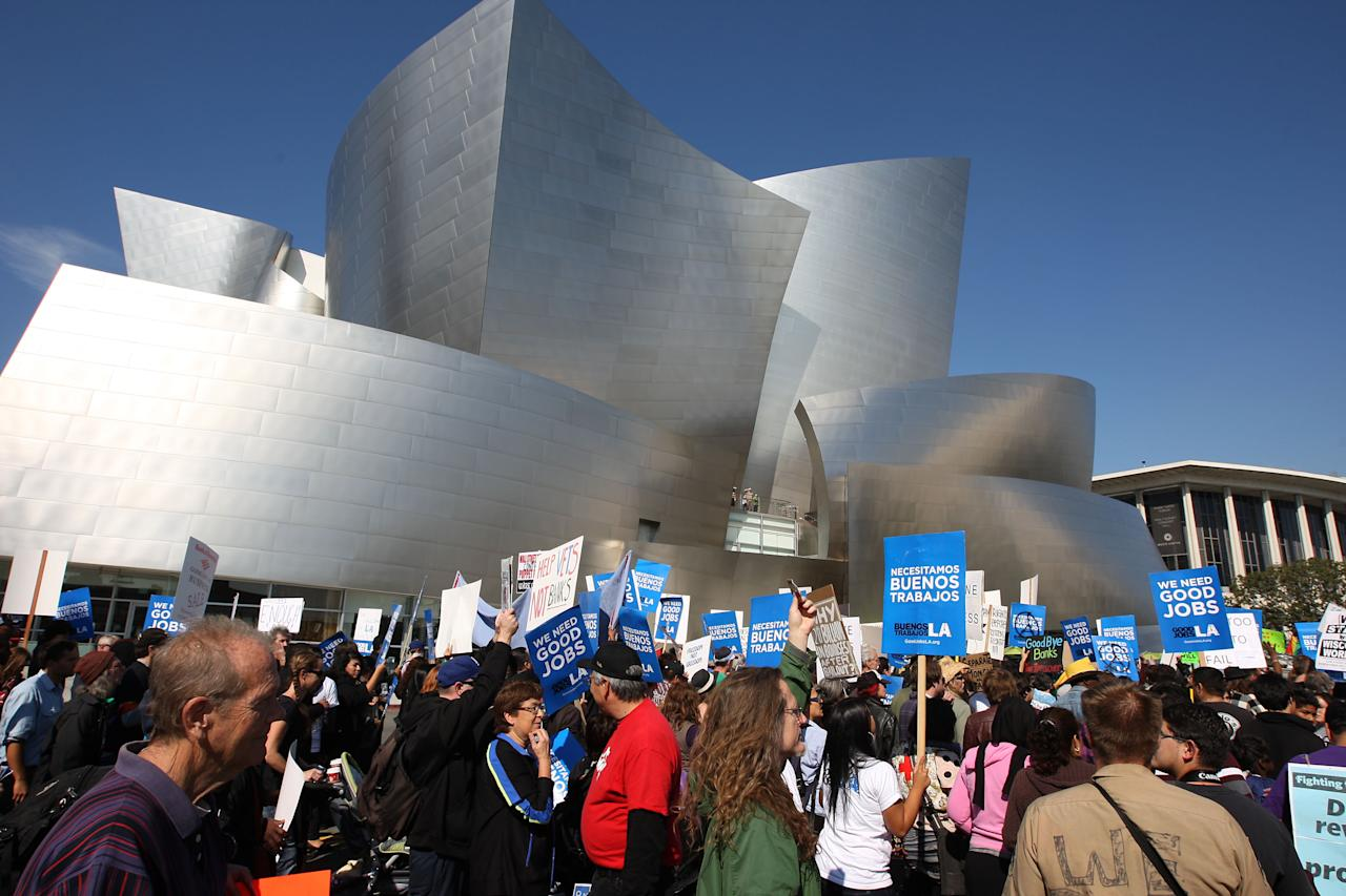 LOS ANGELES, CA - NOVEMBER 5:  Occupy LA protesters pass Disney Hall during the Move Your Money March on what is being called Bank Transfer Day on November 5, 2011 in Los Angeles, California. Occupy movement members are calling for people to move their money from banks to credit unions today in support of the 99% movement.   (Photo by David McNew/Getty Images)