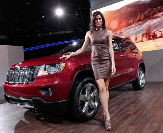 Model Alison Fiori poses next to a 2012 Jeep Grand Cherokee Limited on the final press preview day for the North American International Auto Show in Detroit, Michigan, January 10, 2012. REUTERS/Rebecca Cook