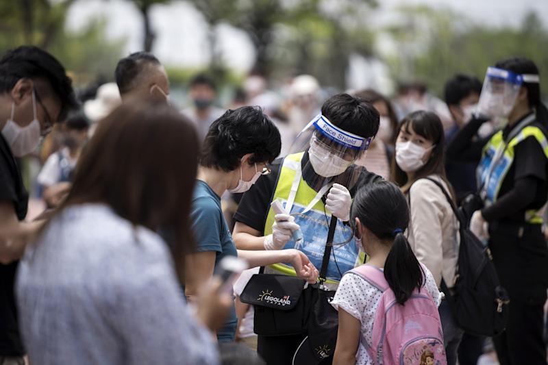 A staff member wearing a face mask measures a visitor's temperature at the entrance to the Legoland Japan theme park (Getty Images)