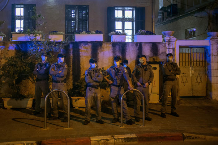 Israeli policemen stand guard at the entrance of a Jewish nationalist religious group's house in the Arab neighborhood of Jaffa, in Tel Aviv, Israel, Saturday, April 24, 2021. Historic Jaffa's rapid gentrification in recent years is coming at the expense of its mostly Arab lower class. With housing prices out of reach, discontent over the city's rapid transformation into a bastion for Israel's ultra-wealthy is reaching a boiling point. (AP Photo/Ariel Schalit)