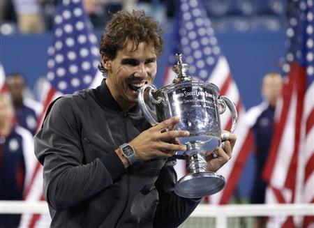 Rafael Nadal of Spain bites his trophy after defeating Novak Djokovic of Serbia in their men's final match at the U.S. Open tennis championships in New York, September 9, 2013. REUTERS/Mike Segar