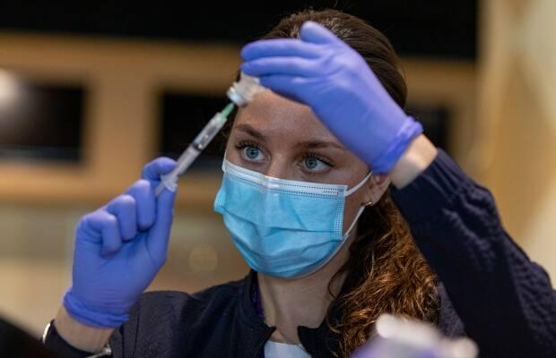 Registered nurse Sarah Moslehi prepares a dose of the Pfizer-BioNTech COVID-19 vaccine at a temporary clinic in Toronto. (Evan Mitsui/CBC - image credit)