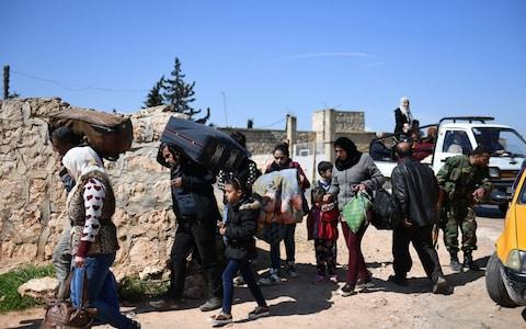 Civilians fleeing Afrin after Turkey said its army and allied rebels surrounded the Kurdish city in northern Syria, walk towards a Kurdish and Syrian pro-regime forces check point  - Credit: AFP