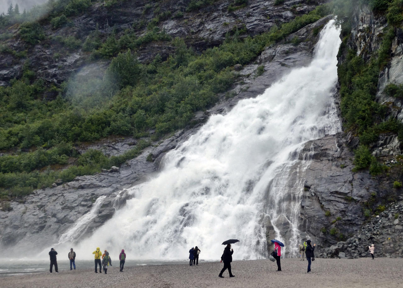 In this photo taken Sunday, July 15, 2018, visitors gather near the base of Nugget Falls on a rainy day in Juneau, Alaska. The falls are a popular destination for cruise ship passengers visiting the city and for locals alike. (AP Photo/Becky Bohrer)