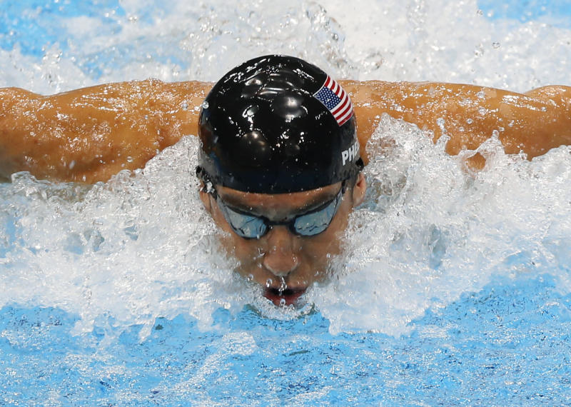 FILE - In this Aug. 4, 2012, file photo, United States' Michael Phelps swims in the men's 4 X 100-meter medley relay at the Aquatics Centre in the Olympic Park during the 2012 Summer Olympics in London. Phelps is coming out of retirement, the first step toward possibly swimming at the 2016 Rio Olympics. Bob Bowman, the swimmer's longtime coach, told The Associated Press on Monday, April 14, 2014, that Phelps is entered in three events — the 50- and 100-meter freestyles and the 100 butterfly at his first meet since the 2012 London Games at a meet in Mesa, Ariz., on April 24-26. (AP Photo/Julio Cortez, File)
