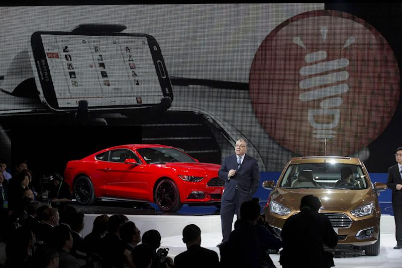 Marin Burela, president & CEO of Changan Ford Automobile Co., Ltd. unveils the Ford Escort sedan, right, during press day at the China Auto show in Beijing, China, Sunday, April 20, 2014. Ford Motor Co. on Sunday unveiled the new Escort sedan designed in China for global sale at a Beijing auto show that highlighted the growing influence of Chinese tastes on the industry. (AP Photo/Ng Han Guan)