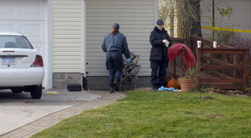 State Police investigators put on gloves and shoe booties before entering the home where a couple was stabbed in Yale, Mich., early Friday, Nov. 12, 2010. Two men were arrested Friday in a brutal and bloody knife attack that left a man dead in his rural Michigan home not far from where his wife _ who suffered more than 20 stab wounds _ taught junior high school. Officers caught the suspects, whose names were not released, about 9:30 a.m., 6 to 7 miles from where the attack occurred in Yale, a village of about 2,000 people surrounded by farms and cornfields. (AP Photo/Times Herald, Mark R. Rummel)