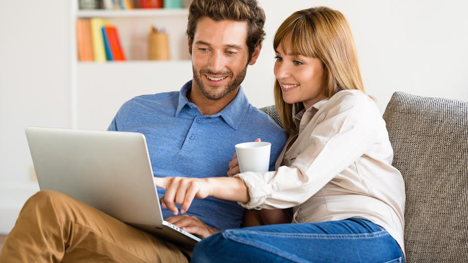 couple sitting on couch and happily looking at laptop