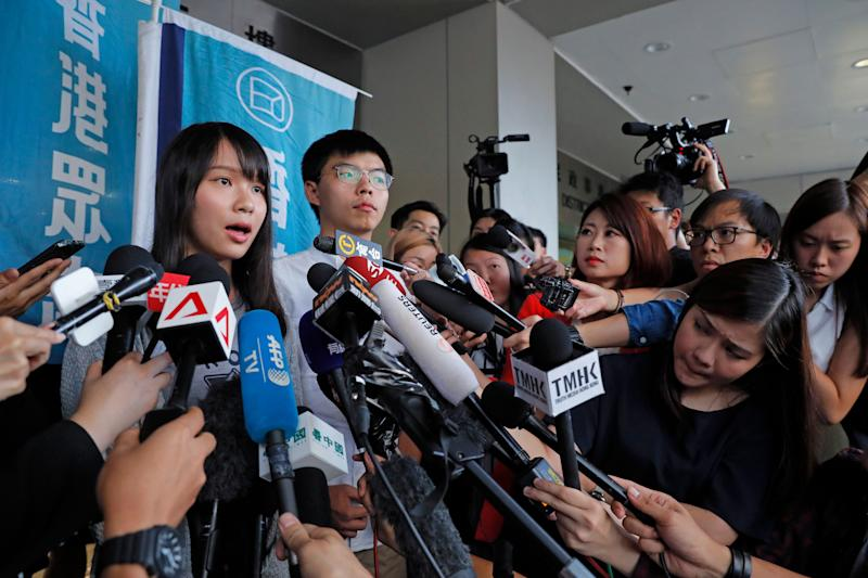 Pro-democracy activists Joshua Wong, right, and Agnes Chow speak to media outside a district court in Hong Kong, Friday, Aug. 30, 2019. Hong Kong activist Joshua Wong and another core member of a pro-democracy group were granted bail Friday after being charged with inciting people to join a protest in June, while authorities denied permission for a major march in what appears to be a harder line on this summer's protests. (AP Photo/Kin Cheung) (Photo: ASSOCIATED PRESS)