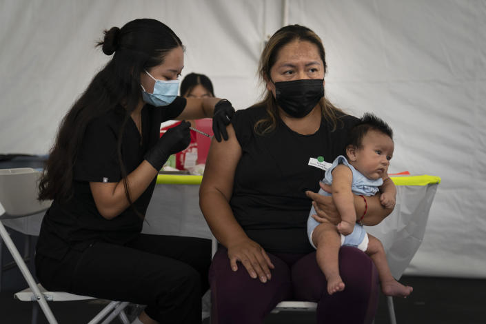 FILE - In this Aug. 28, 2021, file photo, Laura Sanchez, right, holds her 2-month-old son, Lizandro, while receiving the Pfizer COVID-19 vaccine from registered nurse, Noleen Nobleza at a vaccine clinic set up in the parking lot of CalOptima in Orange, Calif. COVID-19 deaths in the U.S. have climbed to an average of more than 1,900 a day for the first time since early March, with experts saying the virus is preying largely on a select group: 71 million unvaccinated Americans. (AP Photo/Jae C. Hong, File)