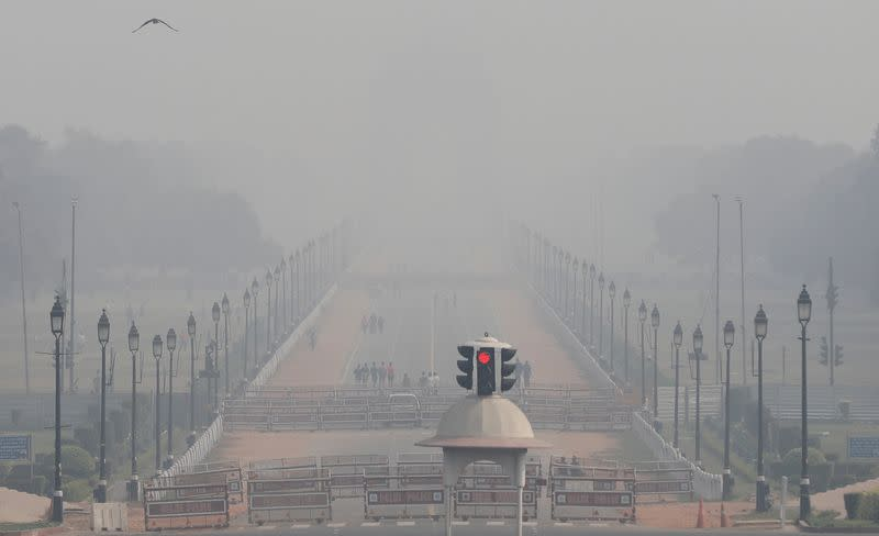 FILE PHOTO: People walk near India Gate on a smoggy afternoon in New Delhi