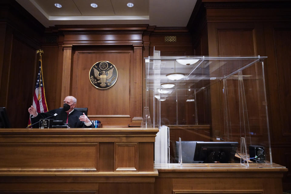 "U.S. District Judge P. Kevin Castel is seen on the bench next to a witness box that is surrounded in plexiglass and contains a HEPA air filter, in a Manhattan federal courtroom, Friday, March 12, 2021, in New York. Castel, who presided over the first two pandemic-era jury trials in the fall, said COVID-19 protocols have become routine. ""Once everybody gets into the rhythm and the flow, after the first day or day and a half it feels very much...like any other trial."" (AP Photo/Mary Altaffer)"