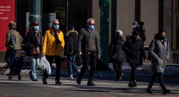 Toronto residents go about their day on Feb. 25, 2021. But the third wave of COVID-19 is here and variants of concern are driving it, the medical officers of health say.