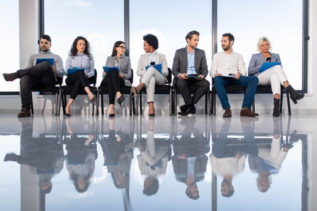 Large group of entrepreneurs sitting on chairs in waiting room before their job interview. Their reflection is seen in floor. Copy space. (Photo: skynesher via Getty Images)