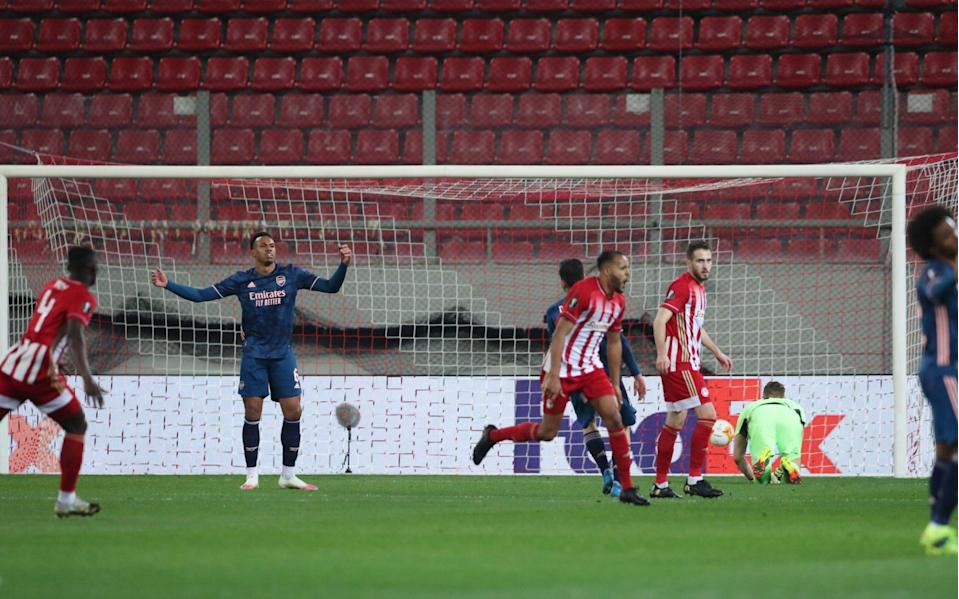 Olympiacos' Youssef El-Arabi celebrates scoring their first goal as Arsenal's Gabriel Magalhaes - Reuters