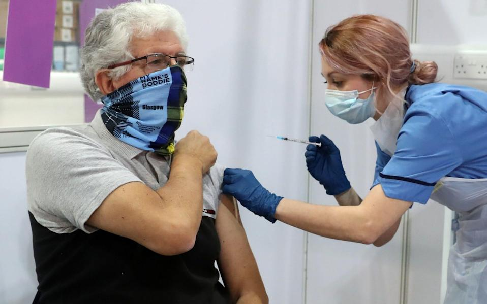 69 year old John Loch from Glasgow receives his Covid-19 vaccination from vaccinator Nicole Clark at the NHS Louisa Jordan Hospital in Glasgow. -  Andrew Milligan/PA Wire