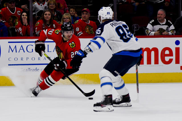 Chicago Blackhawks left wing Brandon Saad (20) moves the puck past Winnipeg Jets center Mathieu Perreault (85) During the first period of an NHL hockey game Saturday, Oct. 12, 2019, in Chicago. (AP Photo/Matt Marton)