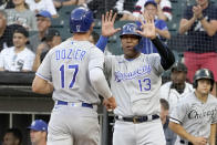 Kansas City Royals' Salvador Perez (13) greets Hunter Dozier at home after they scored on Emmanuel Rivera's double during the first inning of a baseball game against the Chicago White Sox Thursday, Aug. 5, 2021, in Chicago. (AP Photo/Charles Rex Arbogast)
