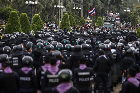 Thai riot police stand guard as anti-government protesters rally inside a compound of the Thai Royal Police Club in Bangkok