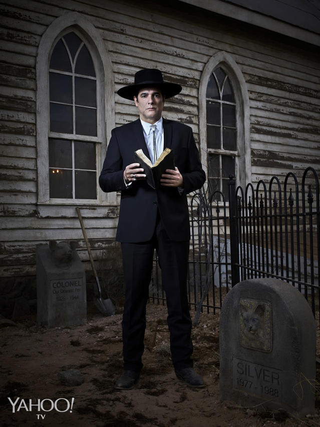 "<p>The reverend (Yul Vazquez, <i>The Good Wife</i>), who appears to take his clothing cues from Johnny Cash, is a quiet thinking man most often seen pouring over his <i>Bible</i> or taking meticulous care of the church's pet cemetery. It's as if he is performing some intense self-imposed penance, which likely has something to do with the fact that he disappears every time there's a full moon rising. Owusu-Breen teases, ""The payoff is so much cooler than your run-of-the-mill werewolf. Shooting the episode where we find out what he is was the coolest thing I have ever been a part of. I could have happily retired.""<br>(Photo: Virginia Sherwood/NBC) </p>"