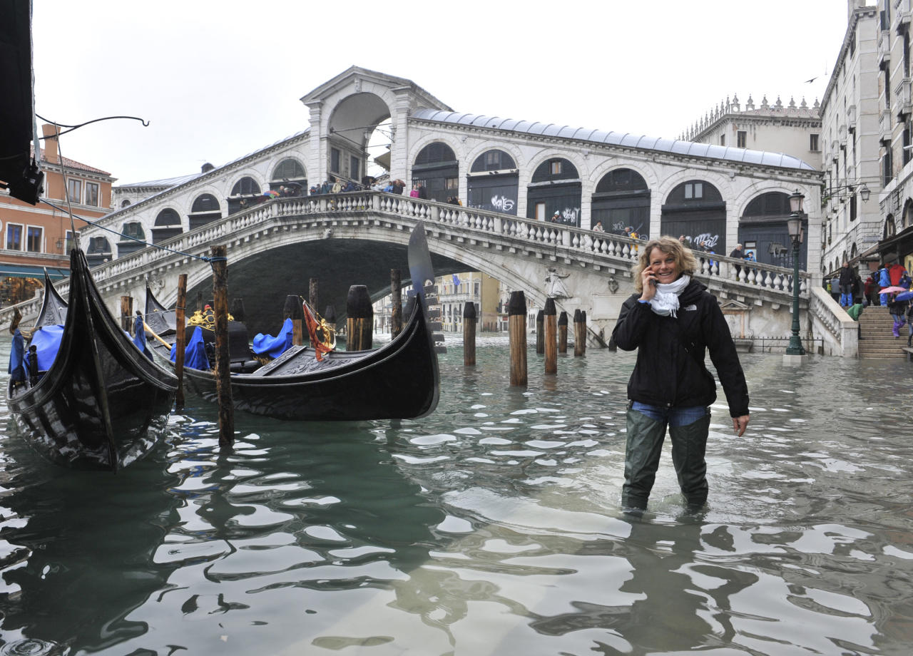 A woman walks in high water ner the Rialto Bridge in Venice, Italy, Thursday, Nov. 1, 2012. High tides have flooded Venice, leading Venetians and tourists to don high boots and use wooden walkways to cross St. Mark's Square and other areas under water. Flooding is common this time of year and Thursday's level that reached a peak of 55 inches (140 centimeters) was below the 63 inches (160 centimeters) recorded four years ago in the worst flooding in decades. (AP Photo/Luigi Costantini)