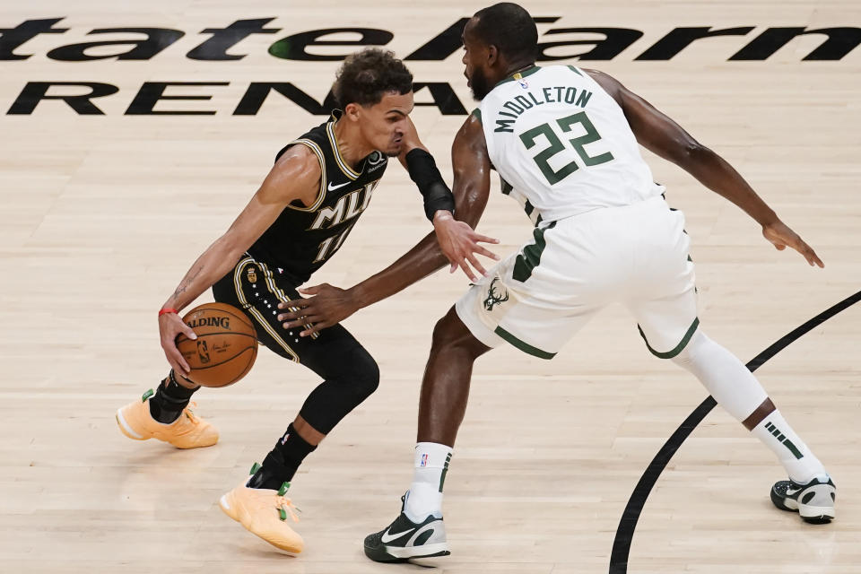 Atlanta Hawks guard Trae Young (11) drives past Milwaukee Bucks forward Khris Middleton (22) during the first half of Game 6 in the NBA basketball playoffs Eastern Conference finals Saturday, July 3, 2021, in Atlanta. (AP Photo/John Bazemore)