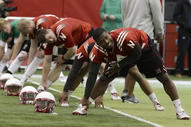Nebraska quarterback Tommy Armstrong Jr. (4) performs stretches in front of other quarterbacks on the first day of spring NCAA college football practice in Lincoln, Neb., Saturday, March 8, 2014. (AP Photo/Nati Harnik)