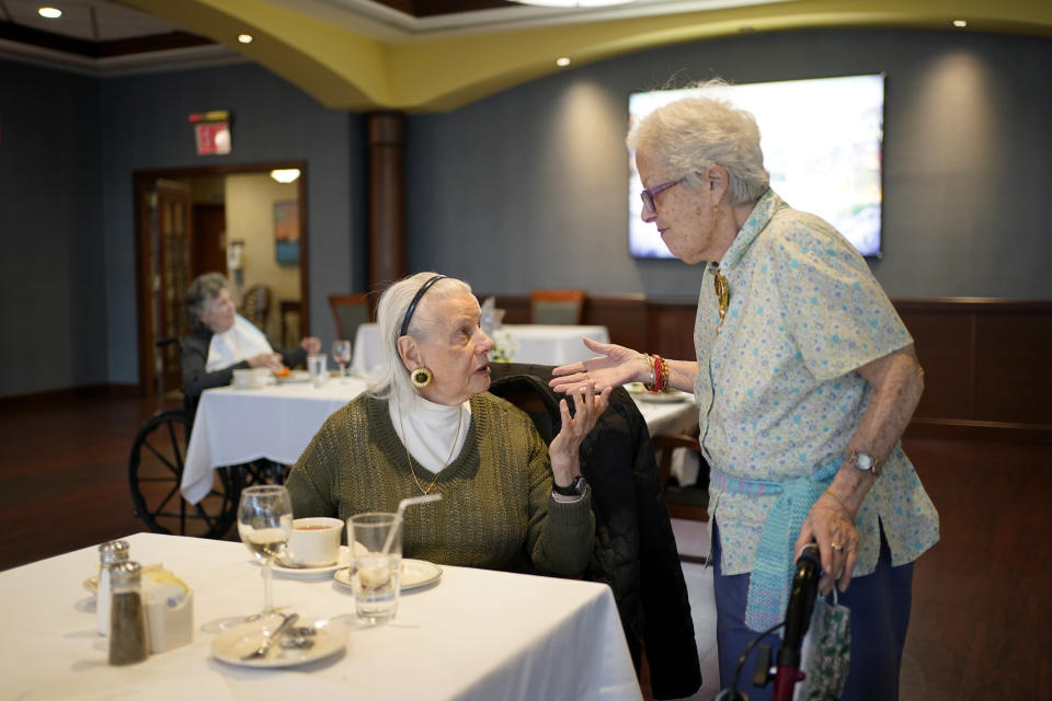 FILE - Ita Aber, right, stops by the table of her old friend Rita Shliselberg after she finished dinner at RiverWalk, an independent senior housing facility, in New York, Thursday, April 1, 2021. Since the start of the pandemic, residents had been dining in their rooms. Only recently have they began to use the dining hall again. A focus on the elderly at the start of the nation's vaccination campaign helped protect nursing homes that were ravaged at the height of the U.S. coronavirus outbreak, but they are far from in the clear. New outbreaks, often traced to infected staff members, are still occurring in long-term care centers across the country, causing continued havoc for visitation policies. (AP Photo/Seth Wenig, File)