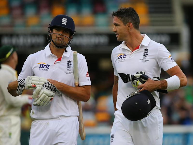 England batsman Alastair Cook (L) and Kevin Pietersen walk on day three of the first Ashes cricket Test match between England and Australia at the Gabba Cricket Ground in Brisbane on November 23, 2013