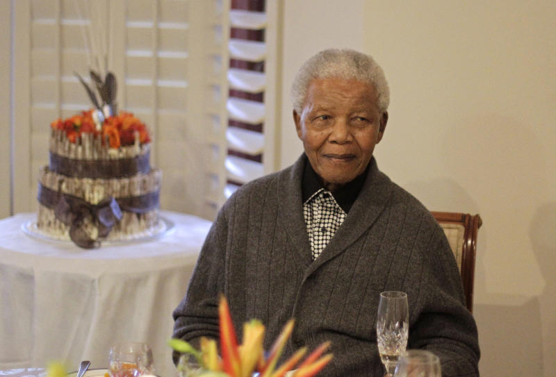 FILE - In this Wednesday, July 18, 2012 file photo, former South African President Nelson Mandela celebrates his birthday with family in Qunu, South Africa. The emotional pain and practical demands facing Nelson Mandela's family are universal: confronting the final days of an elderly loved one. There are no rules for how or when the end may arrive. Mandela's status as a respected global figure only complicates the situation, doctors and end-of-life experts say. (AP Photo/Schalk van Zuydam, File)
