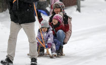 A man pulls his family on a sled at a snowy street in Gelsenkirchen, Germany, Sunday, Feb. 7, 2021. Snow falls extremely seldom in the industrial Ruhr area. (AP Photo/Martin Meissner)