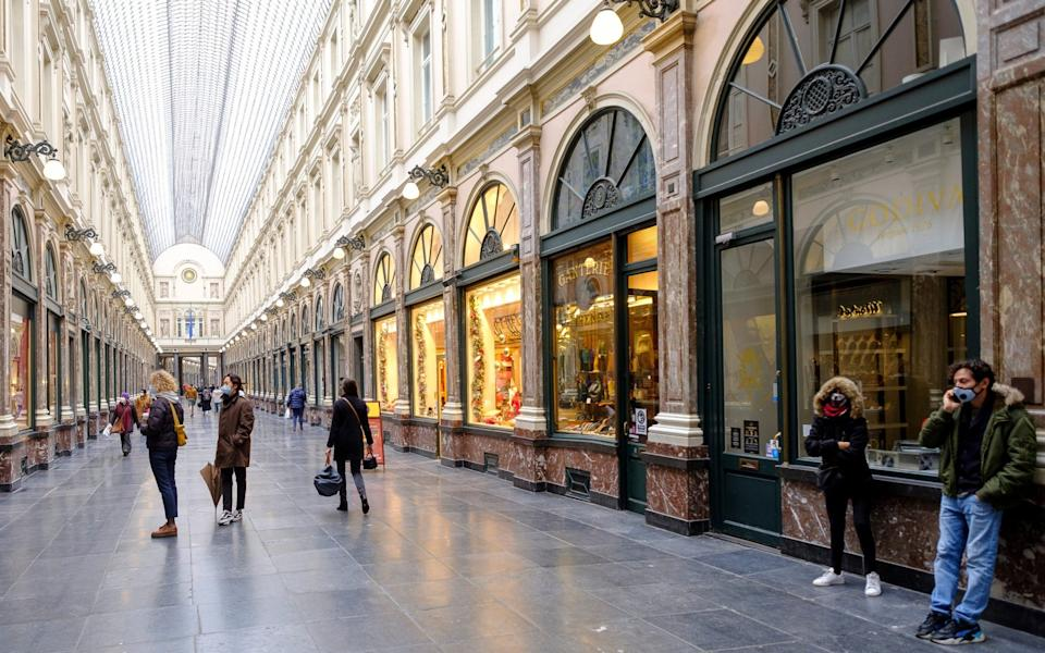 People walk in the near-empty Galeries Royales Saint-Hubert in Brussels - Thierry Monasse/Getty Images