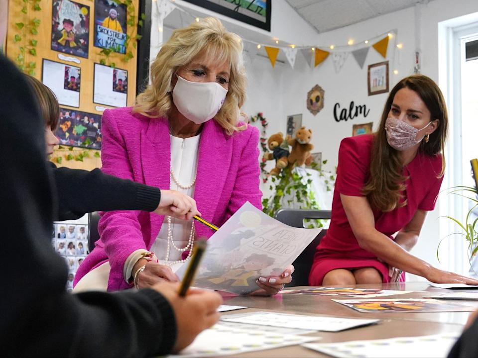 The Duchess of Cambridge (right) and Jill Biden look at a picture of the cover of 'Greta and the Giants' with a reception class at the Connor Downs Academy in Hayle, West Cornwall. Jill Biden is due to meet the Queen on the weekend (PA)