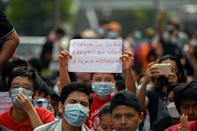 A young protester holds up a sign during a demonstration against the military coup in Yangon on February 6, 2021