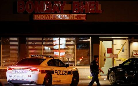 A police officer outside the Bombay Bhel restaurant - Credit: MARK BLINCH/Reuters