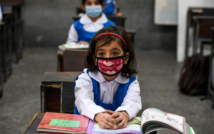 Children wearing facemasks attend a class at a school in Islamabad on September 30, 2020, after the educational institutes reopened primary classes in the third and last phase nearly six months after the spread of the Covid-19 coronavirus - Aamir Qureshi/AFP