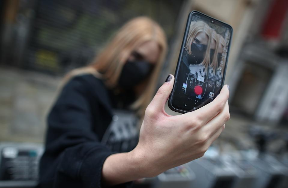 MADRID, SPAIN - SEPTEMBER 24:  Rosa, known as Ghoulbabyghoul in the Tik Tok app where she has more than 3000 followers, records herself with her mobile phone on the Gran Via in Madrid,  on September 24, 2020 in Madrid, Spain.  The ban on downloading the application in the United States, which came into force next Sunday, has been halted following the agreement between Oracle and the company ByteDance, owner of the social network TikTok, according to US President Donald Trump, who has given his blessing to the agreement. (Photo by Eduardo Parra/Europa Press via Getty Images)