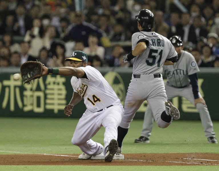 Seattle Mariners' Ichiro Suzuki (51) reaches first past Oakland Athletics first baseman Brandon Allen after hitting a single in the sixth inning of their American League season opening MLB baseball game at Tokyo Dome in Tokyo, Wednesday, March 28, 2012. (AP Photo/Shizuo Kambayashi)