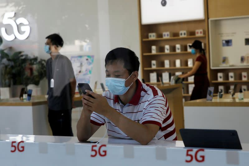 Man checks a mobile phone inside a Huawei store at a shopping mall in Beijing