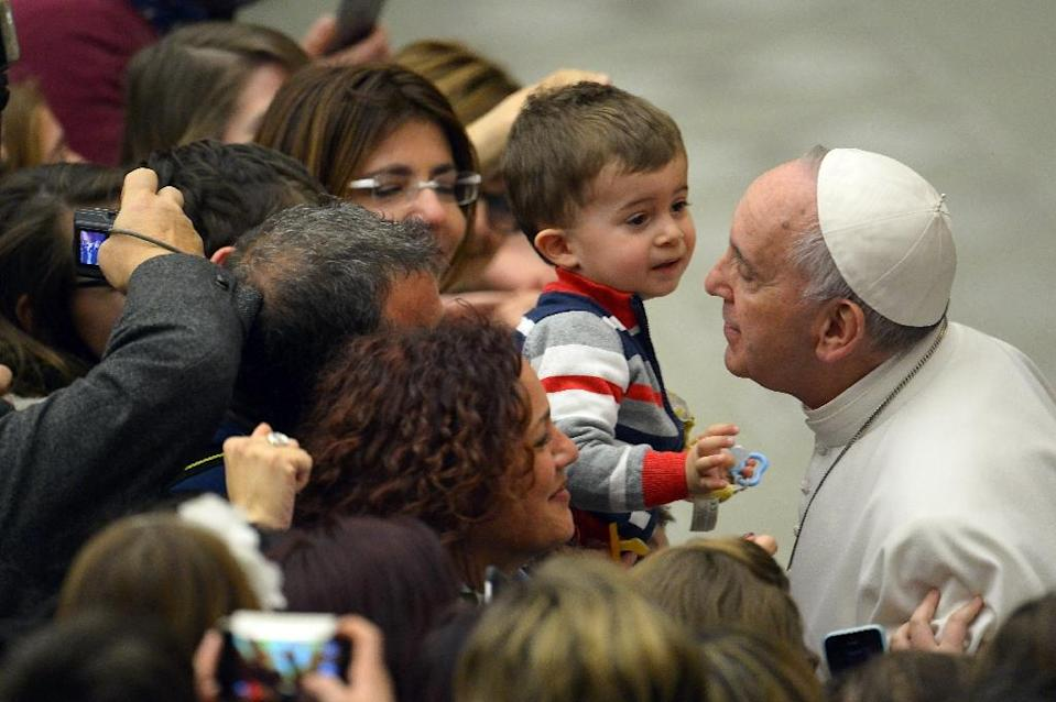 Pope Francis kisses a child during a meeting with members of the Italian union of Catholic teachers, managers, educators and trainers (UCIM) at Paul VI audience hall on March 14, 2015 at the Vatican (AFP Photo/Vincenzo Pinto)