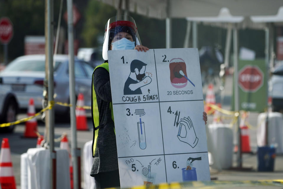 A worker gives instructions to motorists at a COVID-19 testing site Tuesday, Jan. 5, 2021, in Los Angeles. (AP Photo/Marcio Jose Sanchez)