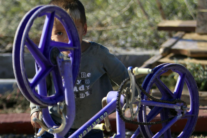 A gypsy child plays with his bicycle , at a gypsy camp near the town of Farsala, some 280 km ( 173 miles) north of Athens, Greece, on Sunday, Oct. 20 , 2013. Greek authorities on Friday, Oct. 18, 2013 have requested international assistance to identify the four-year-old girl found living in a Gypsy camp with a couple arrested and charged with abducting her from her birth parents. A police statement says the child was located Wednesday, Oct. 17, 2013 near the town of Farsala, central Greece, during a nationwide crackdown on illegal activities in Gypsy camps.(AP Photo/Nikolas Giakoumidis)