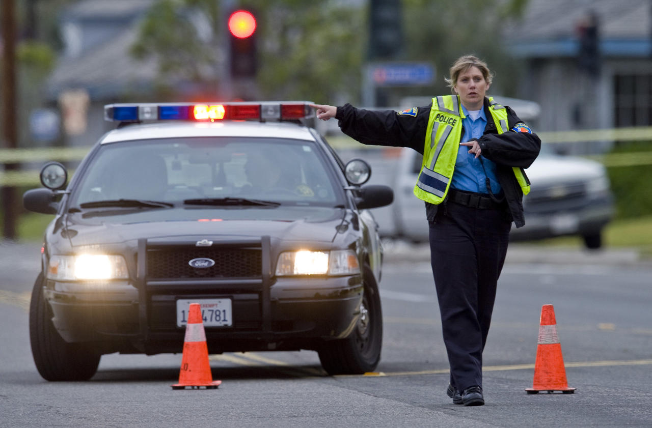 An Orange police officer directs traffic as an investigation of a shooting continues, Tuesday, Feb. 19, 2013 in Orange County, Calif. Police say a chaotic 25-minute shooting spree through Orange County left a trail of dead and injured victims before the shooter killed himself. Orange County sheriff's spokesman Jim Amormino say there are at least six crime scenes with three people, including the suspected gunman, dead and several others wounded. Tustin police Supervisor Dave Kanoti said the shootings started with an apparent carjacking just after 5 a.m. Tuesday in an unincorporated Ladera Ranch area of Orange County. (AP Photo/The Orange County Register, Mark Rightmire) MAGS OUT; LOS ANGELES TIMES OUT
