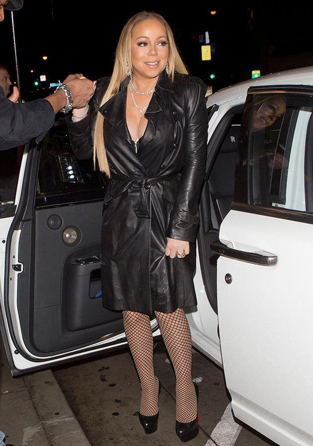 Vamping it up in fishnet tights and a leather trench, Mariah didn't care who noticed her ring bling. Source: Mega