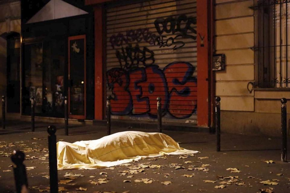 FILE - In this Friday Nov. 13, 2015 file photo a victim under a blanket lays dead outside the Bataclan theater in Paris. In the 20 years since the Sept. 11, 2001 terrorist attacks in the United States, a mixture of homegrown extremists, geography and weaknesses in counterterrorism strategies have combined to turn Europe into a prime target for jihadists bent on hurting the West. (AP Photo/Jerome Delay, File)