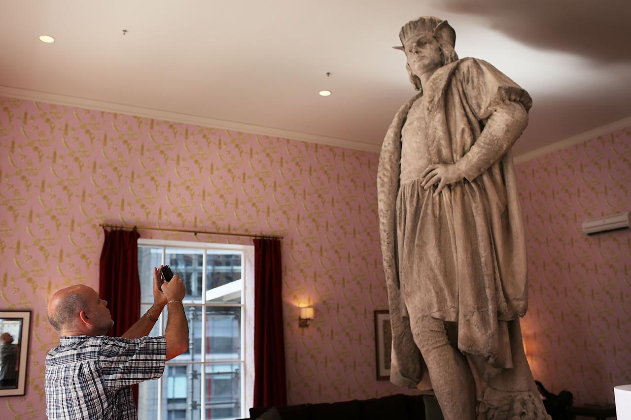 "NEW YORK, NY - SEPTEMBER 19:  A man photographs the iconic 13-foot statue of Christopher Columbus is viewed from the 810-square-foot ""living room"" art installation by Japanese artist Tatzu Nishi on September 19, 2012 in New York City. Viewed as a piece of conceptual art, ""Living Room"", which sits 70-feet above ground level and is only accessible via a scaffold-encased staircase, has been temporarily built around the Columbus Monument in Columbus Circle. Beginning Thursday, up to 25 people at a time can enter the living room to view up close the 1892 marble figure of the Italian explorer.  (Photo by Spencer Platt/Getty Images)"