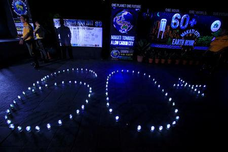 Glasses with lights lamps form the number 60, representing the 60 minutes of Earth Hour, during Earth Hour in Makati city, metro Manila, Philippines March 25, 2017. REUTERS/Romeo Ranoco